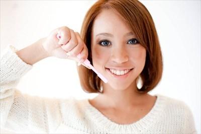笑顔で歯ブラシを持つ人物